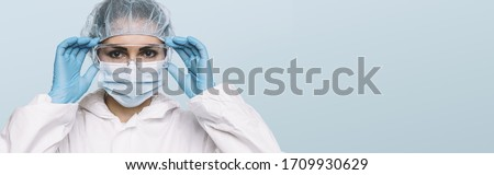 Female Doctor or Nurse Wearing latex protective gloves and medical Protective Mask and glasses on face. Protection for Coronavirus COVID-19, with copyspace for your individual text.