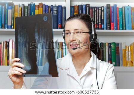 Female doctor or radiologist with headset and an x-ray of a foot in hand as seen through a webcam, telehealth concept