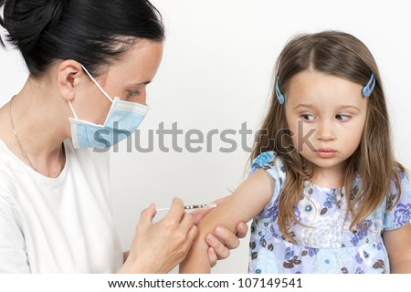 female doctor pediatrician with breathing mask over mouth giving child an intramuscular injection in arm