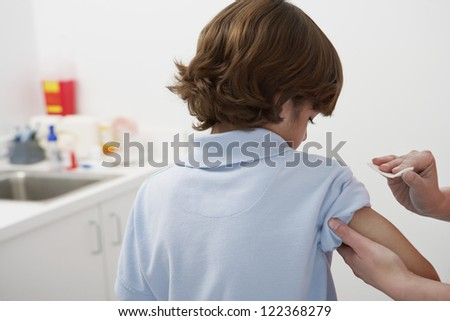 Female doctor's hand rubbing tissue paper before injection