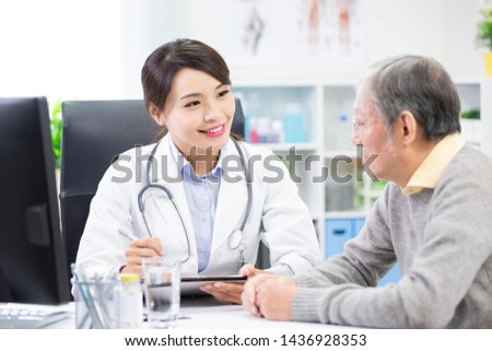 Female doctor see elder patient and discuss with him patiently