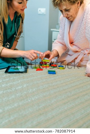 Female doctor showing geometric shape game to elderly female patient with dementia #782087914