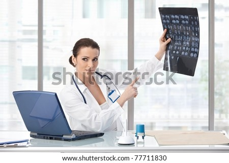 Female doctor sitting at desk explaining medical scan, looking away, smiling.?