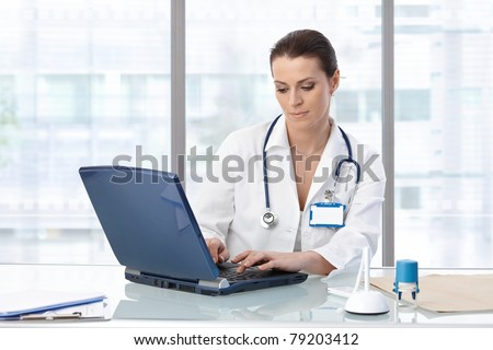 Female doctor sitting at table with laptop, looking down, working.?