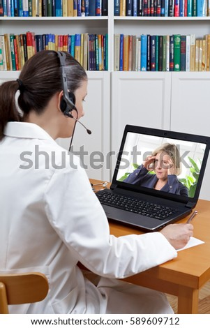 Female doctor sitting at the desk of her office with headphones and laptop, listening to patient with strong headaches, telehealth concept