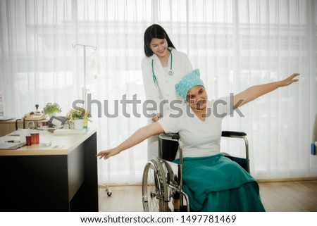 Female doctor takes care of a female patient with cancer, sits at the wheelchair, and wants her to be cheerful, relaxed, and act like a flying bird, enjoying the disease in the hospital diagnosis room #1497781469