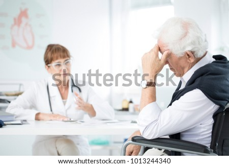 Female doctor talking to a depressed senior patient in her office