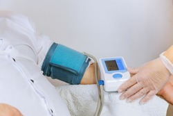 Female doctor to measuring with medical tonometer to measure pressure on the patient arm