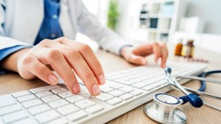 Female doctor typing on computer