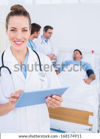 Female doctor using digital tablet with colleagues and patient behind in the hospital