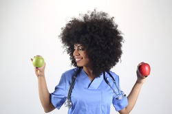 Female doctor with an apple in her hand, afro woman white background, concept of healthy life, health
