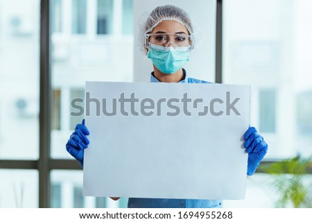 Female doctor with protective workwear holding empty cardboard while standing at clinic and looking at camera. Copy space.
