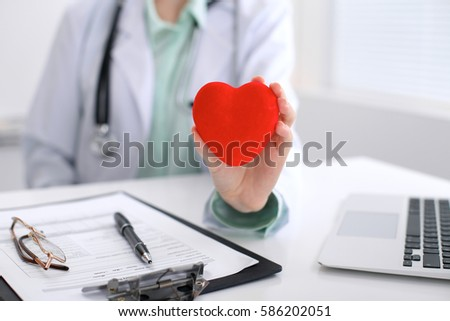 Female doctor with stethoscope holding heart.   Cardio therapeutist, physician make cardiac physical, heart rate measure, arrhythmia, old age life concept #586202051