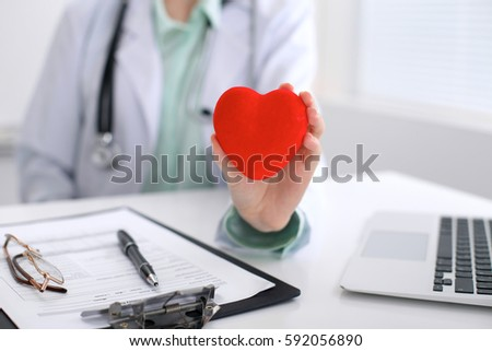 Female doctor with stethoscope holding heart.   Cardio therapeutist, physician make cardiac physical, heart rate measure, arrhythmia, old age life concept #592056890