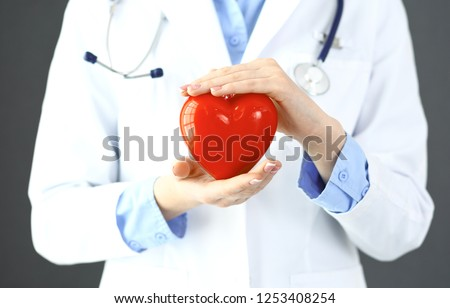 Female doctor with stethoscope holding heart in her arms. Healthcare and cardiology concept  in medicine