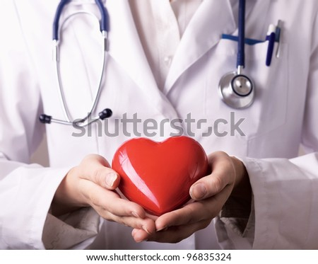 Female doctor with stethoscope holding heart, isolated on white background - stock photo