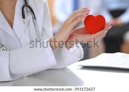 Female doctor with stethoscope holding heart.  Patients couple sitting in the background #393172627