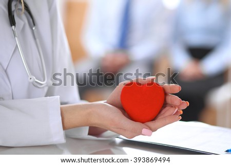 Female doctor with stethoscope holding heart.  Patients couple sitting in the background #393869494