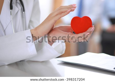 Female doctor with stethoscope holding heart.  Patients couple sitting in the background #398317204