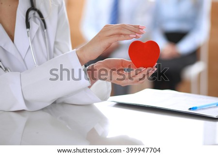 Female doctor with stethoscope holding heart.  Patients couple sitting in the background #399947704