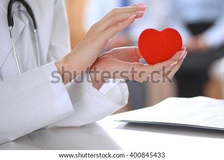 Female doctor with stethoscope holding heart.  Patients couple sitting in the background #400845433
