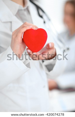 Female doctor with stethoscope holding heart.  Patients couple sitting in the background #420074278