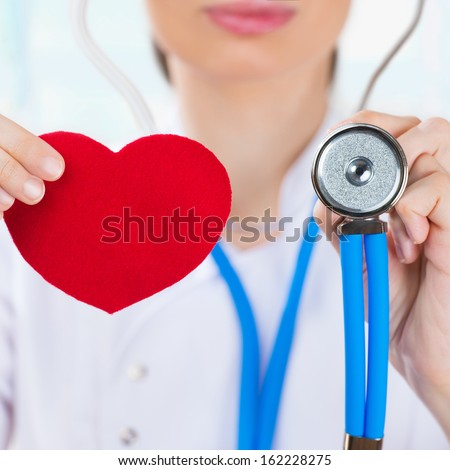 Female doctor with stethoscope holding red human heart at hospital