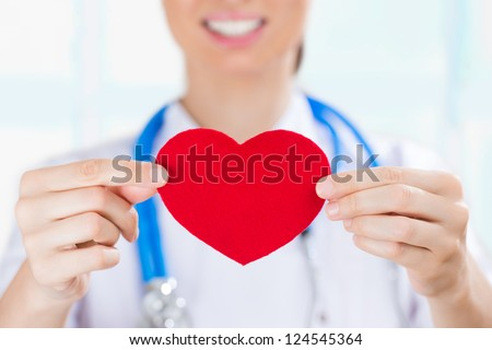 Female doctor with stethoscope holding red human heart at hospital, life insurance and follow up program concept