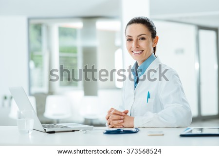 Female doctor working at office desk and smiling at camera, office interior on background #373568524