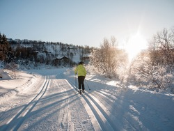 Female doing her cross-country morning ride in a perfect groomed track in the norwegian mountains when the sun rise above the montain edge creating bright sunrays and casting long terrain shadows