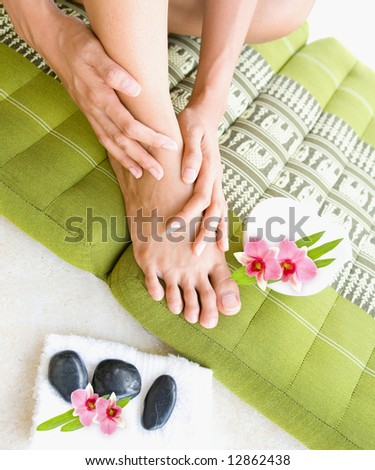 Female doing self foot massage with aromatherapy oil