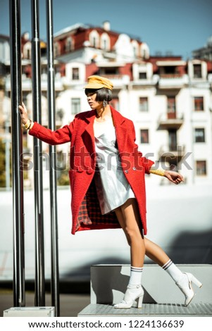 Female dramatically staying. Attracting authentic girlfriend elegantly posing with silver pipes nearby covered in warm red overcoat
