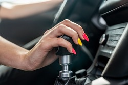 female driver hand shifting gear shift knob manually before the beginning of the ride