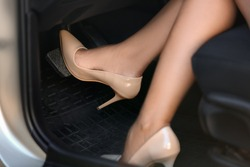 Female driver in high-heeled shoes pushing car break pedal
