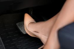 Female driver in high-heeled shoes pushing car break pedal, closeup