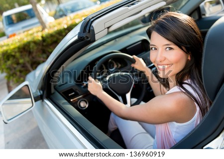 Female driver looking very happy driving a car - stock photo