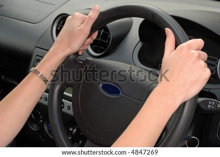 Female driving vehicle showing correct hand position on steering wheel