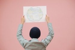 Female eco activist in a cap holding planet earth banner above head. Over pink background. She's also wearing turquoise leather jacket.