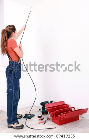 Female electrician pulling cable through wall