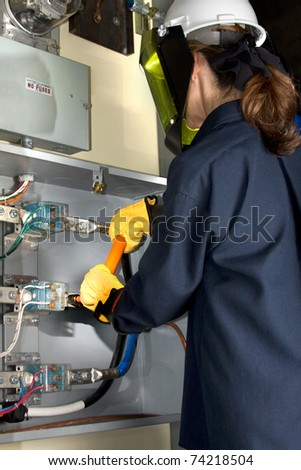 Female Electrician with protective clothing performing work in an energized panel. All trade marks removed or modified.