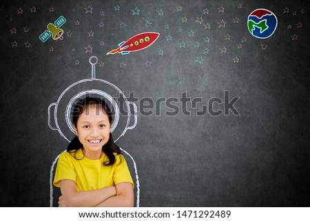 Female elementary school student smiling at the camera while imagining being an astronaut #1471292489