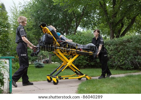 Female emergency medical team transporting senior patient on stretcher