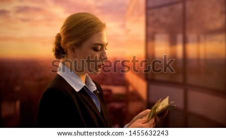 Female employee counting money, dissatisfied with salary, low company earnings #1455632243