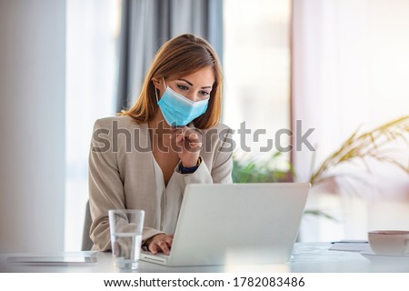 Female employee wearing medical face mask while working in the business office during covid-19 pandemic. Businesswoman wearing face mask while analzying reports in the office.