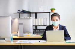 Female employee wearing medical facial mask working alone as of social distancing policy in the business office during new normal change after coronavirus or post covid-19 outbreak pandemic situation