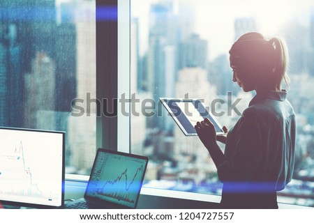 Female employee work on digital tablet standing at office window with skyscrapers view.Silhouette of businesswoman holding in hands touch pad studying online financial banking market on touch pad