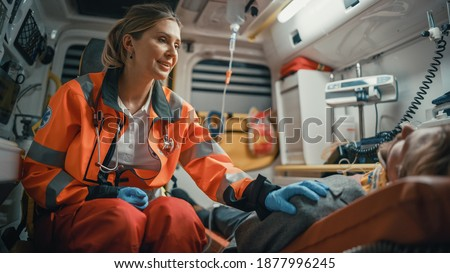 Female EMS Professional Paramedic Comforting Injured Patient on the Way to Hospital. Emergency Medical Care Assistant Puts Her Hand on Vinctim's Shoulder in a Friendly Way in an Ambulance.