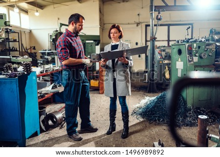 Female engineer consulting with machinist holding manufactured metal part by the lathe machine at industrial manufacturing factory