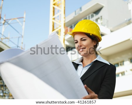 female engineer looking at blueprints in construction site