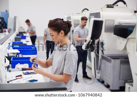 Female Engineer Quality Controlling Components In Factory